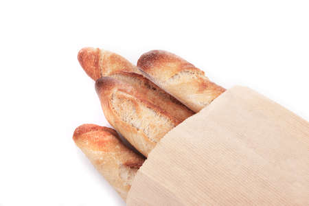 Four crusty French baguettes in a paper bag, isolated on white. photo