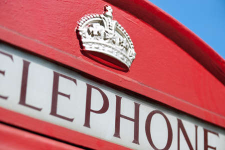 Detail of an old red British Telephone Box. Focus on the crown. photo