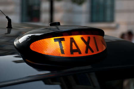 taxi sign: Illuminated London taxi sign, ready for hire.