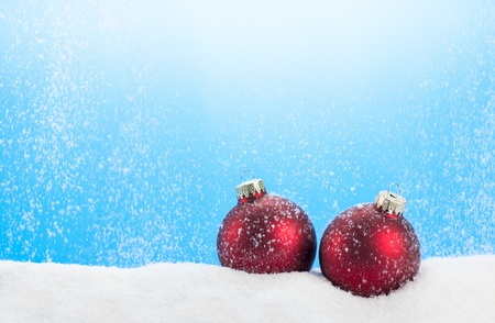 Snowing scene with two red Christmas baubles.