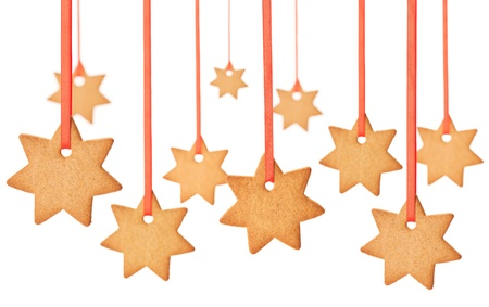 Delicious gingerbread Christmas stars, hanging on red ribbons over isolated background.