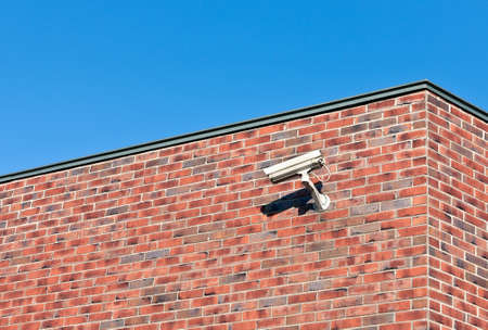 Modern white surveillance camera mounted on an old brick wall building. photo
