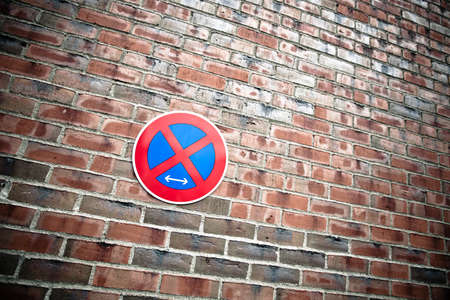 raod: No Parking sign on a vignetted old brick wall.
