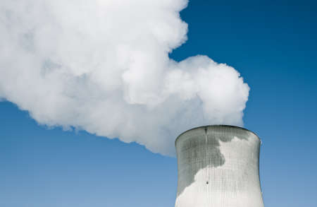 close up chimney: Nuclear Power Station with steaming tower over clear blue sky.