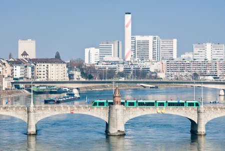 Typical scene at the Rhine river in the center of Basel, Switzerland  Middle Bridge with green tramway, a boat passing the Rhine river at the very center of Basel  Stock Photo