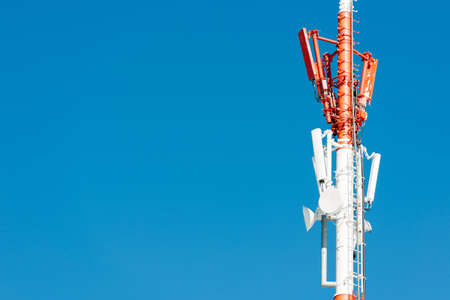 Red-white communication tower over blue sky with copy space  photo