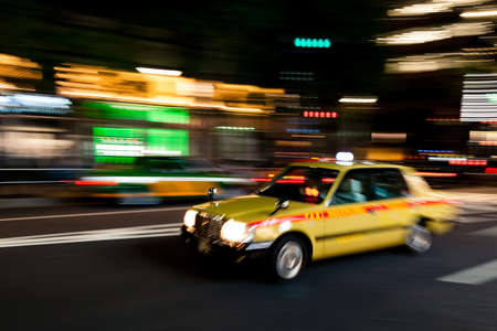 Yellow Tokyo taxi rushing through Tokyo downtown district at night
