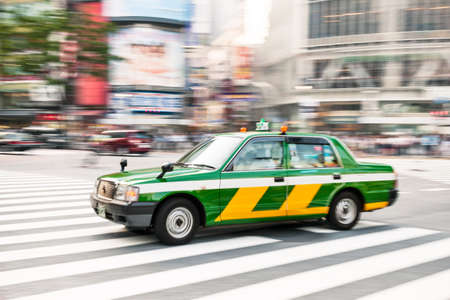 tokyo prefecture: Traditional Tokyo taxi rushing over Shibuya crossing, one of the most crowded places in Tokyo  Blurred Motion  Stock Photo