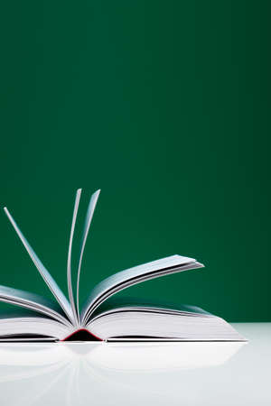 medium close up: Single book on a white desk with flying pages over green background