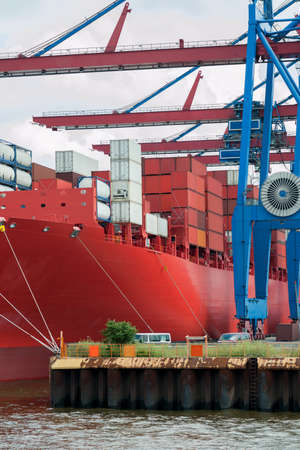 containership: Large red containership docked at the pier of a container terminal
