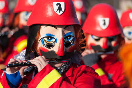 Traditional flute players in a vibrant red firefighters costume with black and white Basel coat of arms on their helmets.