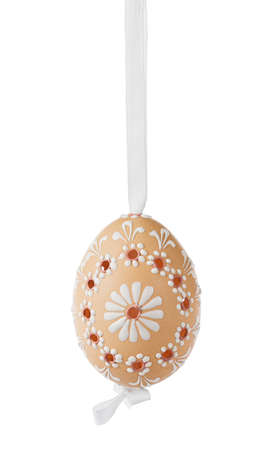 Traditional caved easter egg, decorated with flower, hanging on a white ribbon. Isolated on white. photo