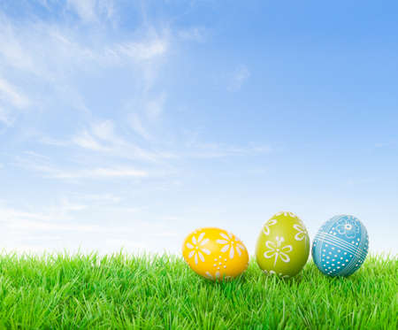 egg hunt: Colorful easter eggs on meadow over bright spring sky. Stock Photo