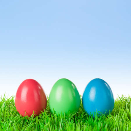 Three red green blue colored easter eggs on a meadow over a bright clear sky. photo