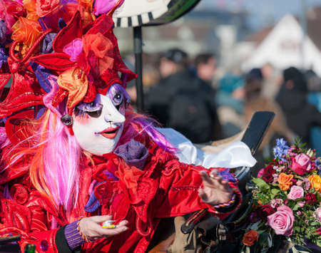 fasnacht: Old lady costume giving sweets at fasnacht festival while sitting in an old carriage