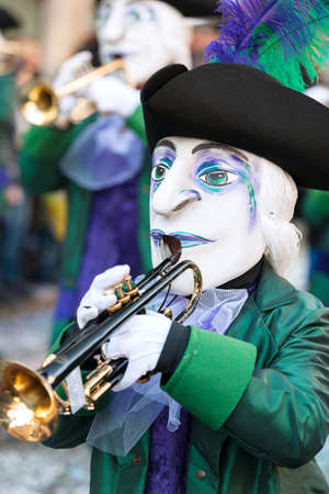 fasnacht: Group of medieval masks in green and purple costumes playing trumpet at Fasnacht Festival Basel, Switzerland Editorial