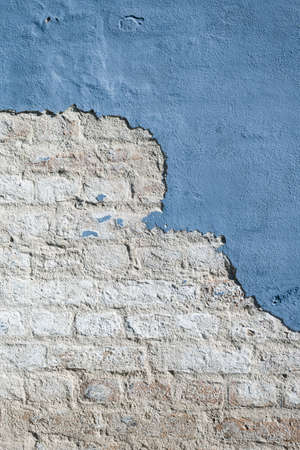Old blue painted brick wall with blue weathered plaster