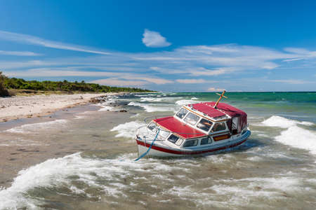beached: Stranded red boat on beach after storm  Stock Photo