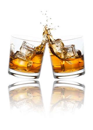 clinking: Dos vasos de whisky tintineo juntos, aislados en blanco