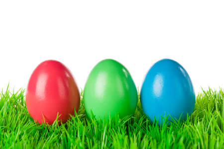 Three red green blue colored easter eggs on a meadow, isolated on white  photo