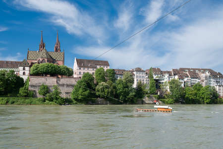 swiss culture: Old ferry crossing the Rhine river at Basel, Switzerland. In the background the famous Basel cathedrale, one of the top spots for tourists.