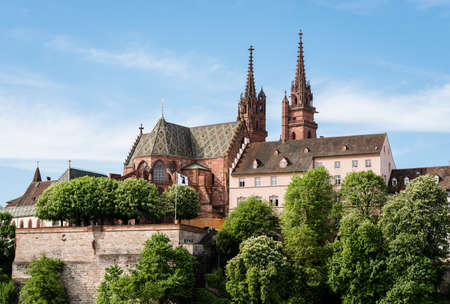 swiss culture: View up to the famous Basel cathedral with observation point and Basel flag.