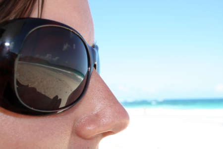 Reflection of the beach in the Glasses of the girl
