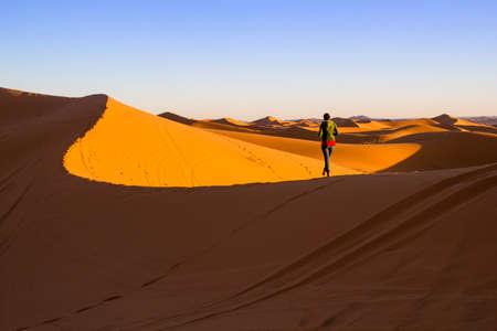 Woman walking on top of a sand dune in Merzouga