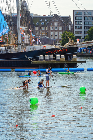 peddle: Peddling on a surfboard at SAIL Amsterdam 2015, the largest free public sail event in the world. AUGUST 20, 2015 AMSTERDAM THE NETHERLANDS
