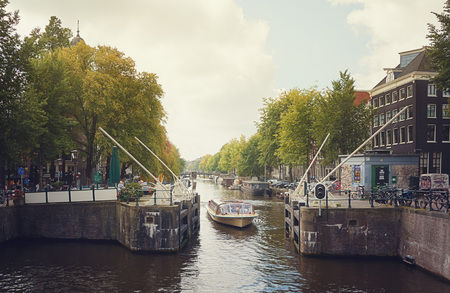 city park boat house: 14 September 2014, a tour boat passes the lock on the Singel canal in Amsterdam, The Netherlands