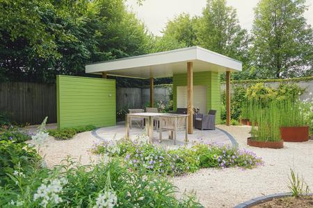 Appeltern, Nederland, 22 juli 2015: De Tuinen van Appeltern is de inspiratie tuin park in Nederland. Op deze foto van een tuin met terras en overhang, versierd met trendy tuinmeubelen en plantenbakken.