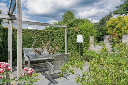 Appeltern, The Netherlands, July 22, 2015: The Gardens of Appeltern is the inspiration garden park in the Netherlands. In this picture a garden with terrace and trendy garden furniture and white standing living room lamp. Editorial