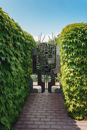 horticulture: Appeltern, The Netherlands, July 22, 2015: The Gardens of Appeltern is the inspiration garden park in the Netherlands. In this picture a garden with a beautiful decorative gate between two hedges. Editorial