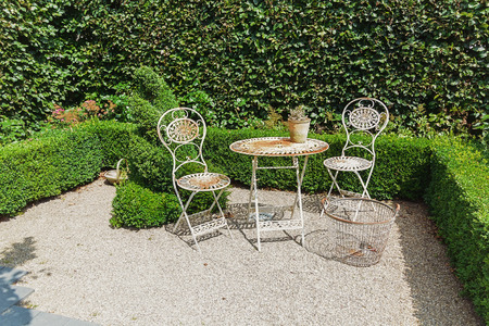 openwork: Openwork iron garden furniture to the background of the hedge.