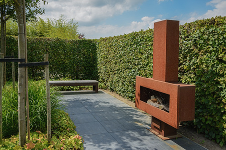 sitting area: Sitting area in the garden with a fireplace and a bench near a hedge.