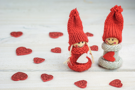 woman hanging toy: Knitted dolls on a wooden table.
