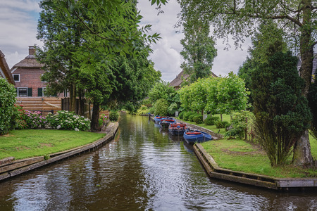 Giethoorn, The Netherlands - June 29, 2016: known for its bridges, waterways, thatched cottages and punts. It is also called the Dutch Venice and known to the world Monopoly edition.