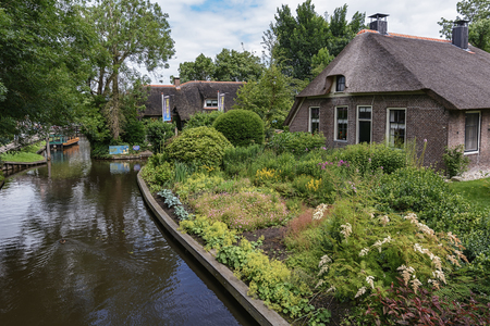 waterways: Giethoorn, Netherlands - June 29, 2016: known for its bridges, waterways,  thatched cottages  and punters. It is also called the Dutch Venice and known to the world Monopoly edition.