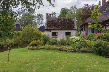 Giethoorn, Netherlands - June 29, 2016: known for its bridges, waterways,  thatched cottages  and punters. It is also called the Dutch Venice and known to the world Monopoly edition.