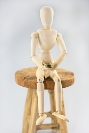 Mannequin sitting on a chair and holding a coin.