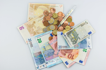 Thermometer on a pile of euros to symbolize the concerns about the euro. Stock Photo