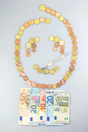 deflation: Sad sick smiley made of Euro coins with a blanket of Euro banknotes with thermometer.
