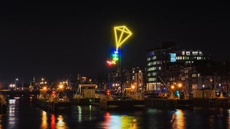 above 18: Amsterdam, Netherlands - December 18, 2015: Light Festival Amsterdam, neon light kite above the port of Amsterdam