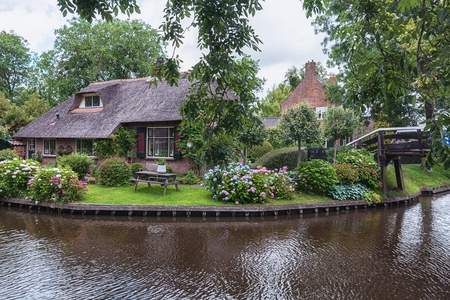 View of a blooming garden in front of the house of the Dutch town.