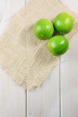 Three lime on the piece of cloth from a sacking on a wooden table. Stock Photo