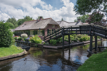 felled: Giethoorn, The Netherlands - June 29, 2016: The bridge leading to the house across the canal in the Dutch town of Giethoorn.