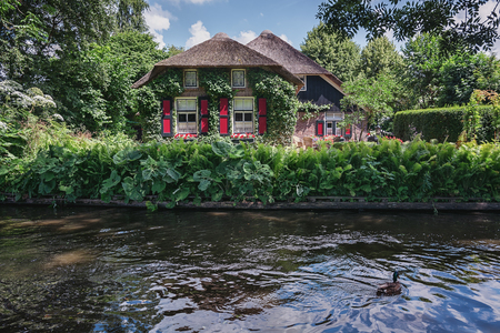 View of a blooming garden in front of the house of the Dutch town Giethoorn.