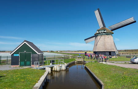 Zijpe, Netherlands - May 1, 2016: participants in the organized walk Flowering seepage measurement at a typical Dutch Windmill in the head of the province of North Holland in The Netherlands.