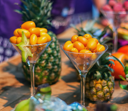 Dwarf orange als known as kumquats served in a glass with on the background pineapples