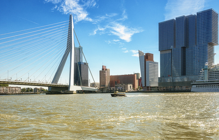 holland: Rotterdam, Netherlands - August 18, 2016: Picture of the Erasmus bridge and the Rotterdam for the building along the Wilhelminakade Has The AIDA cruise ship docked.